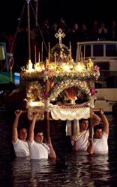 Good Friday, the Epitaphios is transferred into the water in Hydra Island, Greece. Selected by www.oiamansion.com