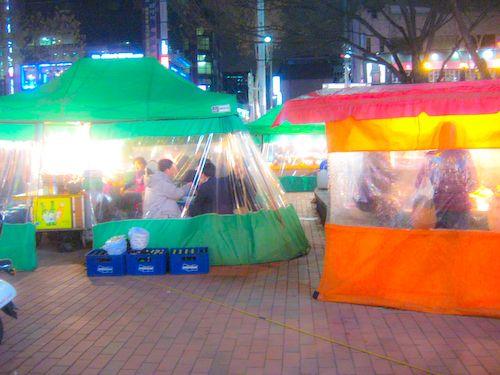 Eat Korean tent food with soju.