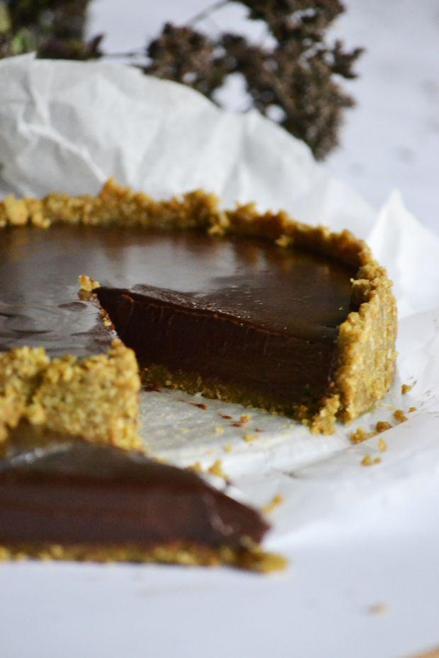 """A világ legjobb sütés nélküli csokitortája Hozzávalók egy 18 centis tortaformához: 20 dkg zabkeksz 7 dkg vaj 1 evőkanál mandula aroma 200 g étcsokoládé 2 dl habtejszín A zabkekszet morzsává darálom. A vajat megolvasztom. A kekszre locsolom a vajat és az amaretto-t, összekeverem, majd belenyomkodom a tortaformába úgy, hogy 2 centis pereme is legyen a """"tésztának"""". Beteszem a hűtőbe legalább 15 percre."""