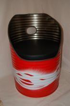 Sillón construido a partir de un bidón de aceite. El cojín está fabricado en polipiel negra con una espuma de alta densidad de 5 cm. Bajo el cojín lleva un asiento fabricado en madera recuperada de palets que le proporciona al cojín una superficie adecuada, además de aumentar su resistencia y estabilidad. Dispone de una asa para moverlo con facilidad. El borde de la chapa está cubierto por una goma proveniente de una funda de cable de comunicaciones reciclado que impide cortarse con el filo.