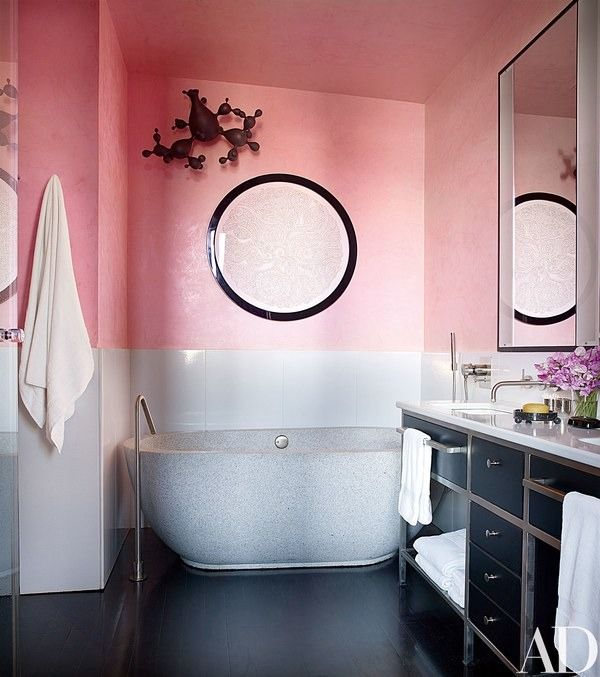 In the master bath, Venetian-plaster walls in Benjamin Moore's Perky Peach serve as the backdrop for a Michael Beatty wall-mounted sculpture and a circular work on paper by Christopher Tanner; the sink and tub fittings are by Boffi, and the towels are by Ralph Lauren Home | archdigest.com