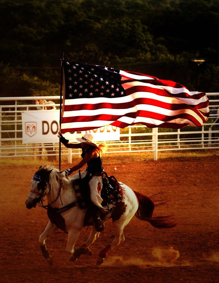 Galloping horse with rider carrying American flag waving in the wind.