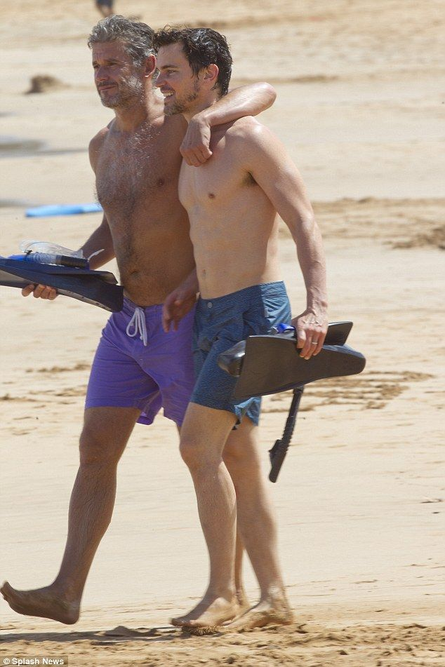 Dynamic duo: Simon, 51, slung his arm around Matt for a trek down the beach, holding onto their snorkeling gear
