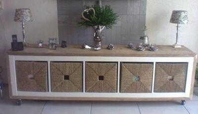 Een Ikea kast bekleden met steigerhout, zwenkwielen eronder, Ikea manden erin en je hebt voor weinig geld een origineel TV meubel.