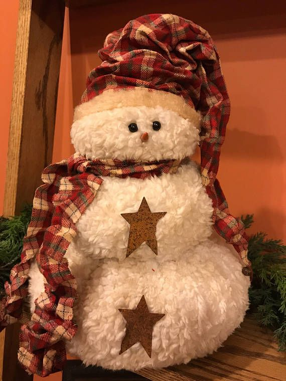 This adorable, slightly primitive snowman is made from 100% polyester Sherpa ivory faux fur that has been lightly coffee stained. He has black beads for eyes and a clay carrot nose. He is wearing a red, green and white cotton flannel scarf and long toboggan with a rusty bell on