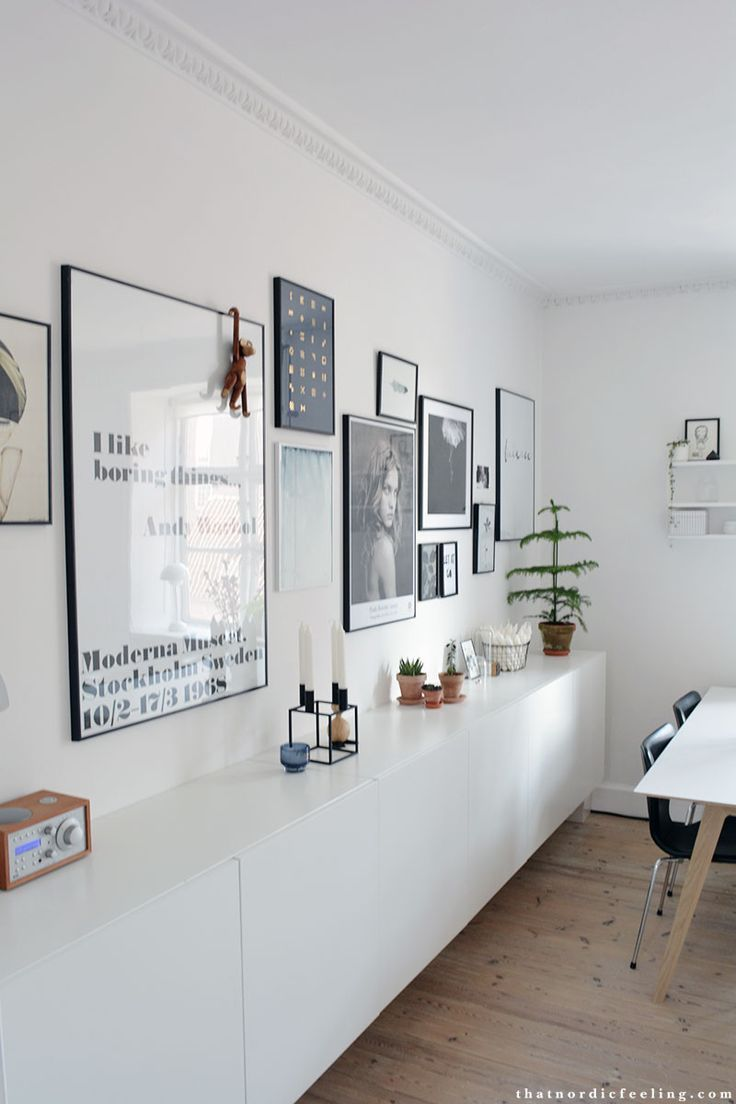Framed prints above a minimal white sideboard.