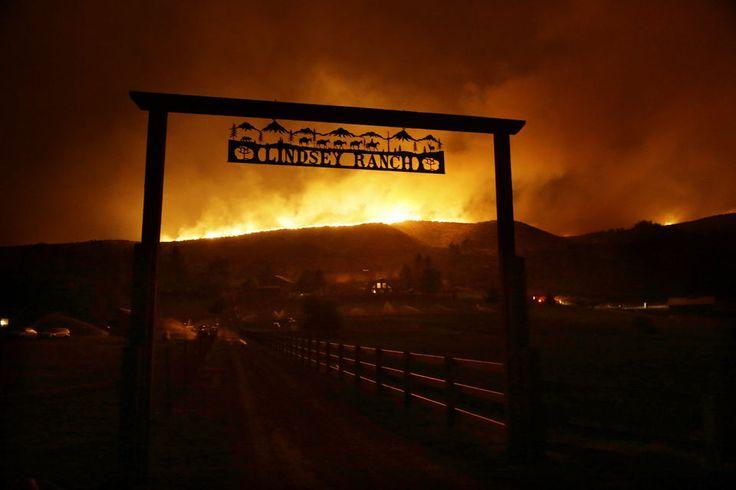 Fire burns on the ridge above a ranch on Twisp River Road in Twisp, Wash.