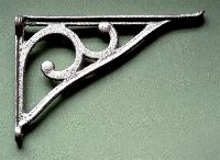 Cast iron simple scroll shelf brackets with a lip on the end of the horizontal.  A lovely simple cast iron shelf bracket, un-fussy and elegant.