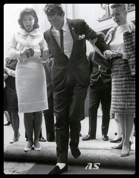Dean Martin putting his footprints in concrete, supported by Claudia and Jeanne