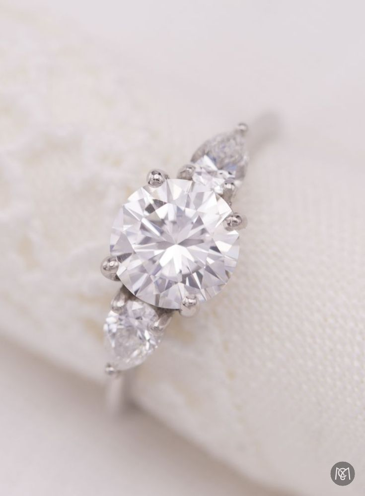 This engagement ring is the absolute definition of modern elegance! A three stone setting with a perfectly tapered platinum shank, two pear-cut diamonds smoothly transitioning from the center stone to the shank, and a gorgeous round brilliant cut diamond as the centerpiece. Simply stunning!