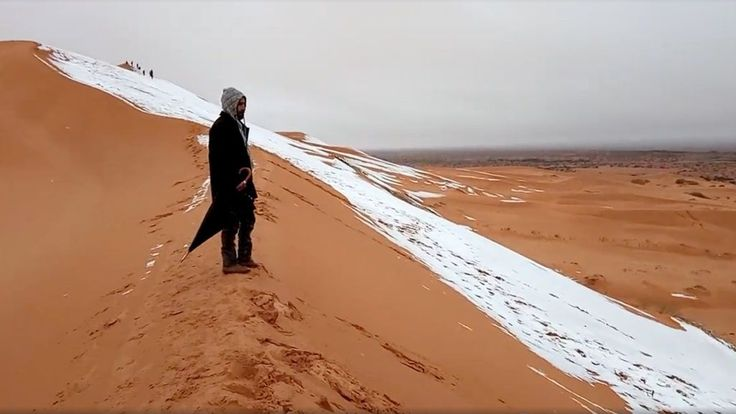 2 méternyi HÓ ESIK a SZAHARÁBAN                           2018.febr.05.    A man looks at at a snow-covered slope in the Sahara, Ain Sefra