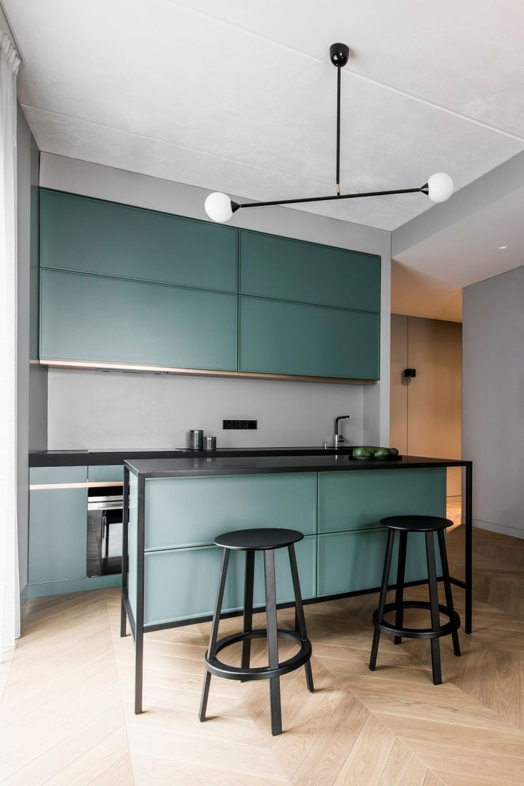 This apartment features an open-plan kitchen, living and dining room with a series of colourful accents, including green cabinets in the kitchen, as well as a velvet blue sofa and textured red chair in the lounge.