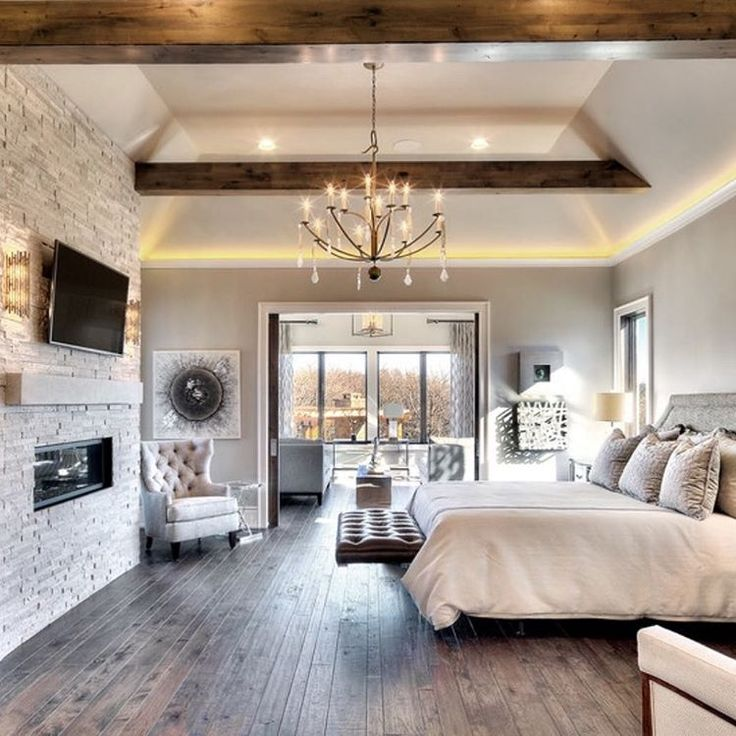 Loving the mix of stone fireplace and wood beams, cozy and inviting! By  Starr Homes master bedroom suite chandelier lighting