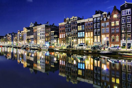Reflections at Night, taken in Amsterdam, The Netherlands (Holland). The glow of lights at night from the skinny tilting houses reflecting in the canals and waterways that runs through Amsterdam