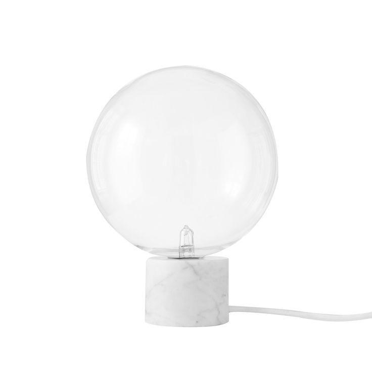 Lampe à poser composée d'une base cylindrique en marbre blanc de Carrare supportant un diffuseur sphérique en verre borosilicate transparent soufflé bouche et équipée d'un câble d'alimentation�...