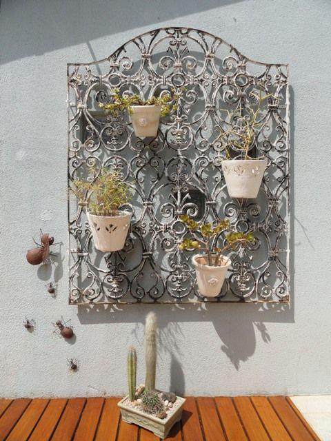 Grade de ferro fundido de janela usado como suporte para vasinhos de plantas