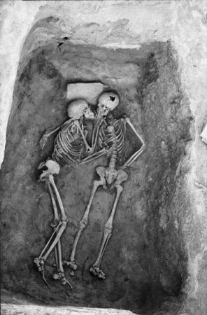 'The Lovers' from 1972 season at Hasanlu Hasanlu is an archaeological excavation site in Iran, Western Azerbaijan, Solduz Valley. These skeletons were found in a Bin with no objects. The only feature is a stone slab under the head of the skeleton on the left hand side. Penn Museum Image #97482.  University of Pennsylvania says their Museum exhibited these 'Hasanlu Lovers' skeletons in 1974, who died together in about 800 B.C.and appear like they are kissing each other before they died
