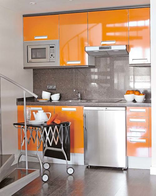 12 Kitchens with Color: This shiny kitchen, spotted on Mi Casa Revista combines doors in bright orange laminate, with steel appliances, and a speckled gray Silestone backsplash and countertop.