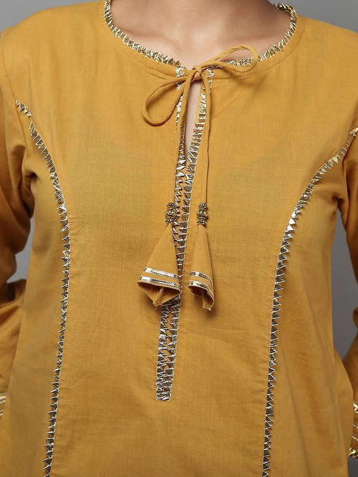 Description: A beautiful tie neck kurta with tassels. It has gota detailing on neck, placket, tassels, princess seams in front & back and sleeves. The lengt
