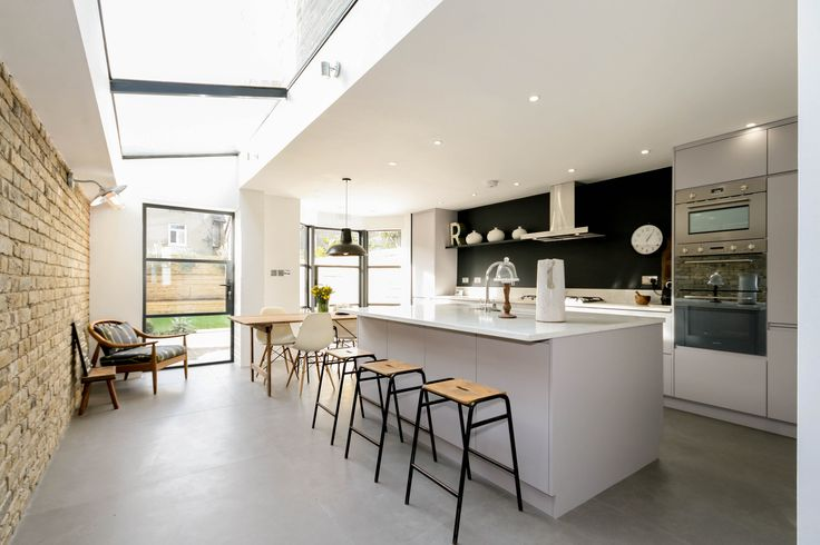 Industrial kitchen with Concrete 1.2m x 1.2m tiles, critical doors and large glass ceiling. Kitchen made by kitchen joiner Matthew Smith