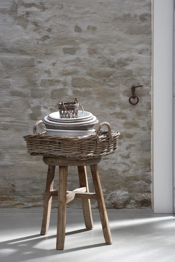 rustic baskets and stool against pale lime washed stone wall