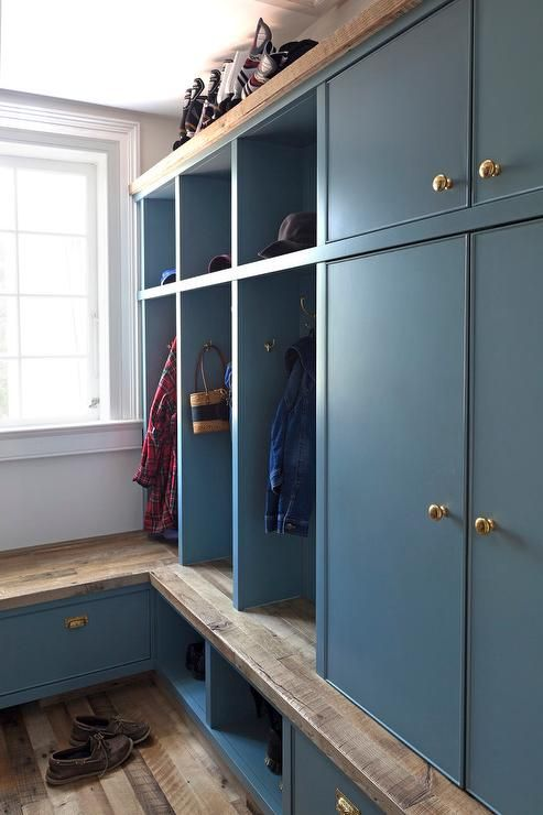 Family friendly mudroom features blue open lockers with overhead cubbies placed atop open shoe cubbies next to a built-in reclaimed wood bench under window. Blue mudroom boasts blue mudroom cabinets adorned with brass knobs alongside a plank wood floor.
