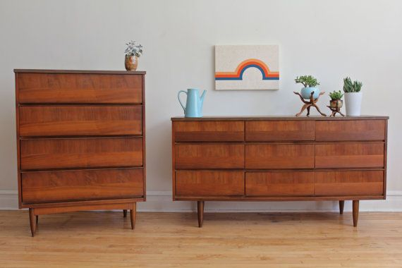 Mid Century Modern matching dressers and mirror. Opposing walnut woodgrains on each drawer. Formica tops in great condition. Matching wooden-framed