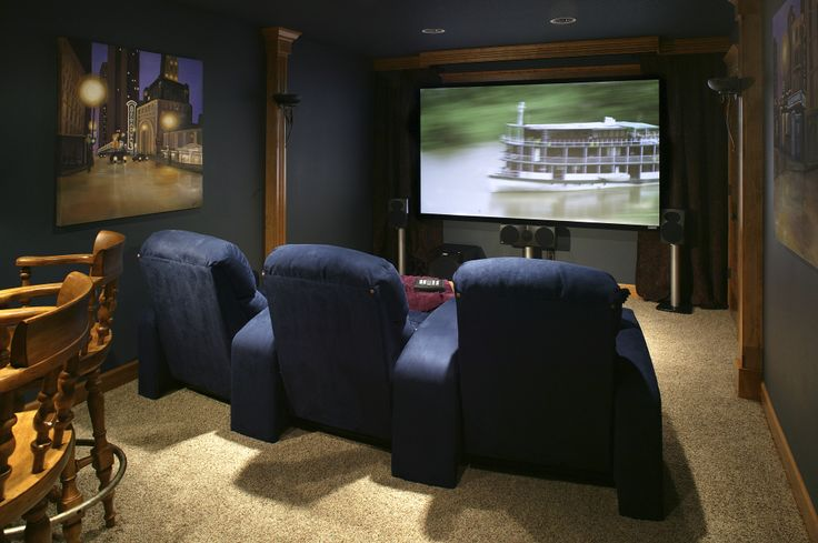 Small home theater featuring a full bar and three navy movie theater seats. Carpeted floors and city wall art completes this remodeled theater.