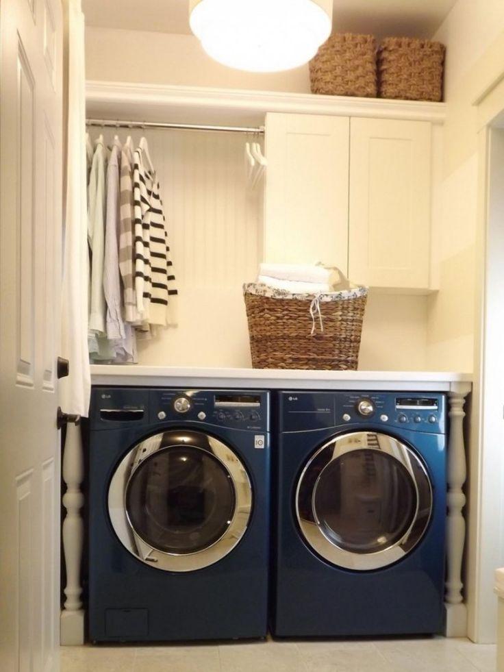 des armoires blanches, une machine à laver et un sèche-linge bleus