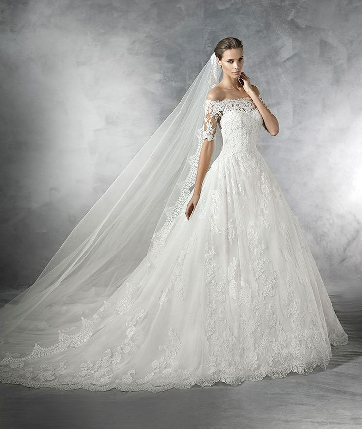 STYLE PLEASANT 2016 PRONOVIAS Princess-style tulle wedding dress. Off-the-shoulder bodice and elbow-length sheer sleeves with lace appliqués. Round neckline and sheer back adorned with appliqués. Tulle and lace skirt with gathers at the waist.
