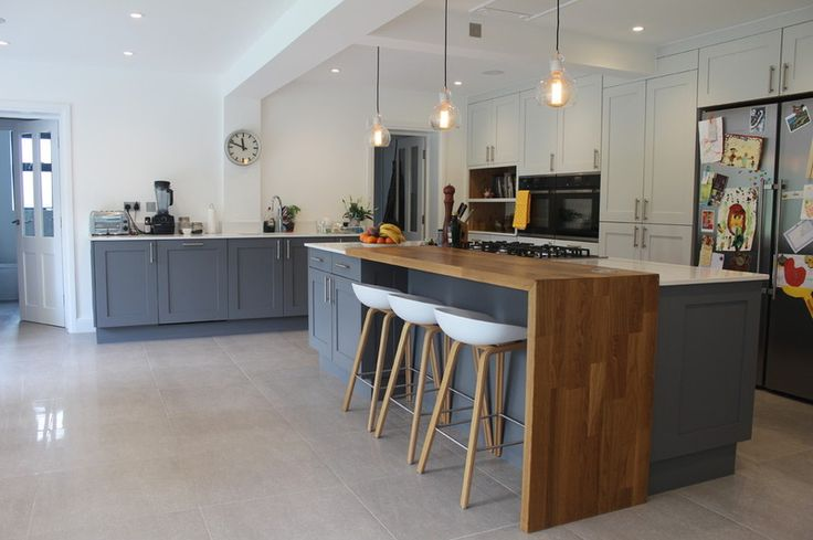 Contemporary Kitchen by Studio 3 kitchens  Little Greene's Dark Lead, and used French Grey Mid on the tall cupboards on the back wall. The elegant wooden stools are from Hee Welling and Hay.