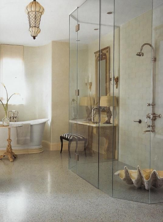 free standing tub with total glass enclosed shower, vintage style nickel hardware, giant clam shell on the mosaic floor, zebra horn leg vanity bench, rustic lamps, gold sconces, moroccan style light fixture, antique iron side table near the tub