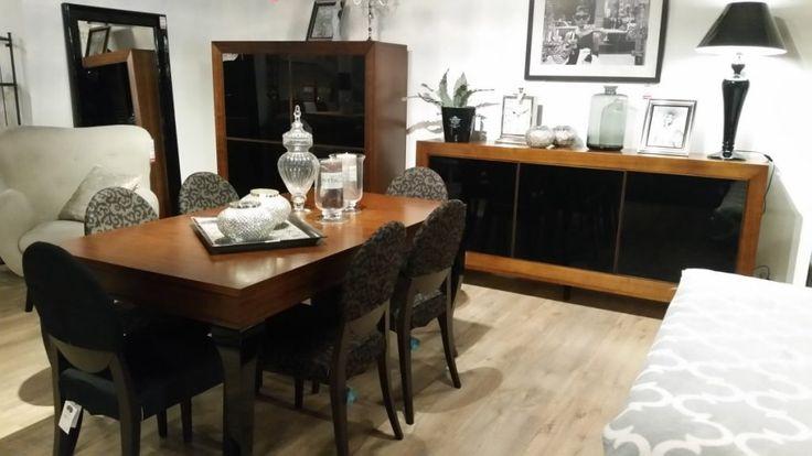 Stół z połyskiem o klasycznym drewnianym blacie w naturalnym kolorze i ozdobnych nóżkach w kolorze czarnym. Krzesła na drewnianych nóżkach z tapicerowanym siedziskiem i oparciem. Uniwersalny zestaw mebli (stół+krzesła) do wnętrz klasycznych, jak i nowoczesnych.