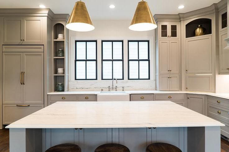 A gray paneled refrigerator accented with brass hardware is positioned under cabinets and beside display shelves fixed next to three black framed windows located above an apron sink completed with a polished nickel deck mount faucet mounted in front of a marble backsplash to a honed Arabescato Danby Marble countertop completing gray shaker cabinets with brass cup pulls.