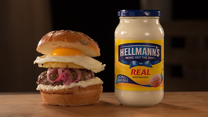 1 barbabietola rossa 2 cucchiai di olio extra vergine di oliva Sale 1 cipolla bianca, tagliata a fette sottili 1⁄4 tazza di aceto bianco 1⁄2 tazza di aceto di riso 2 cucchiai di zucchero 4 fette di ananas peperoncino tritato 2 1⁄2 cucchiai di burro 4 uova grandi 700 gr di macinato misto di carne bovina adatta per burger 4 panini da hamburger tostati Maionese Hellmann's
