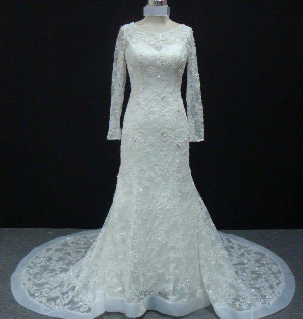 Vestido de noiva semi sereia, com manga longa, de renda e bordado, decote frontal redondo. Via Brasil Noivas.
