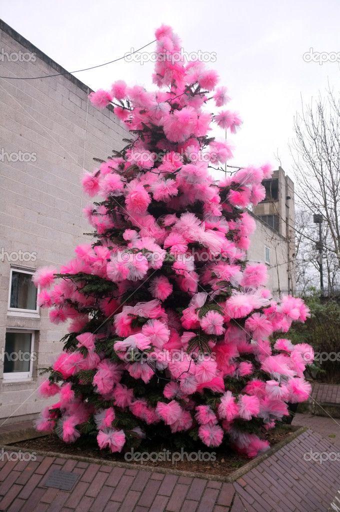 Pino reale all'esterno è decorato con pezza rosa in stile Natale