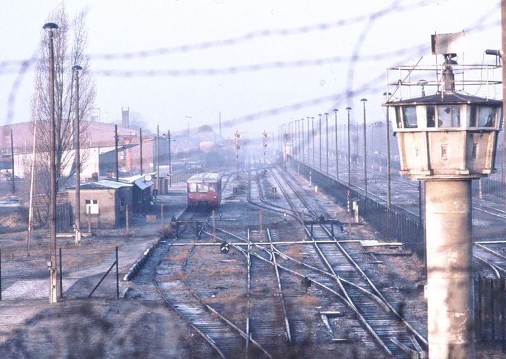 """1961 Berlin - Staaken, Bahnhof Staaken, Blick von Nennhauser Damm / Finkenkruger Weg in West-Berlin (Staaken) rüber zum in der DDR gelegenen Bahnhof Staaken. Die kleine """"Eule"""" (Schienenbus) fährt Richtung Wustermark, Dallgow raus. Rechts im Bild, hinter dem Wachturm, die Transitgleise von und nach West-Berlin.  ☺"""