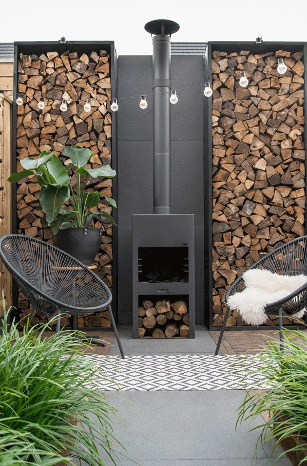 The log burner, log store and modern garden chairs with sheepskin next to the greenery make this a really inviting outdoor space.