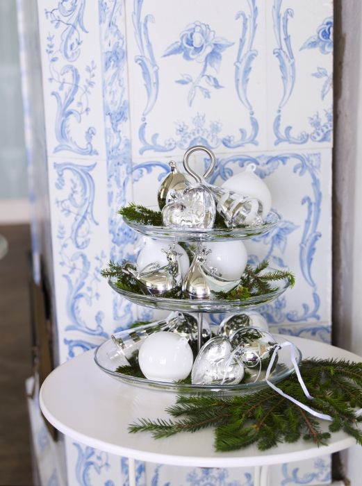 The IKEA 365+ three-tier serving stand filled with ornaments and evergreen makes a festive seasonal centerpiece.
