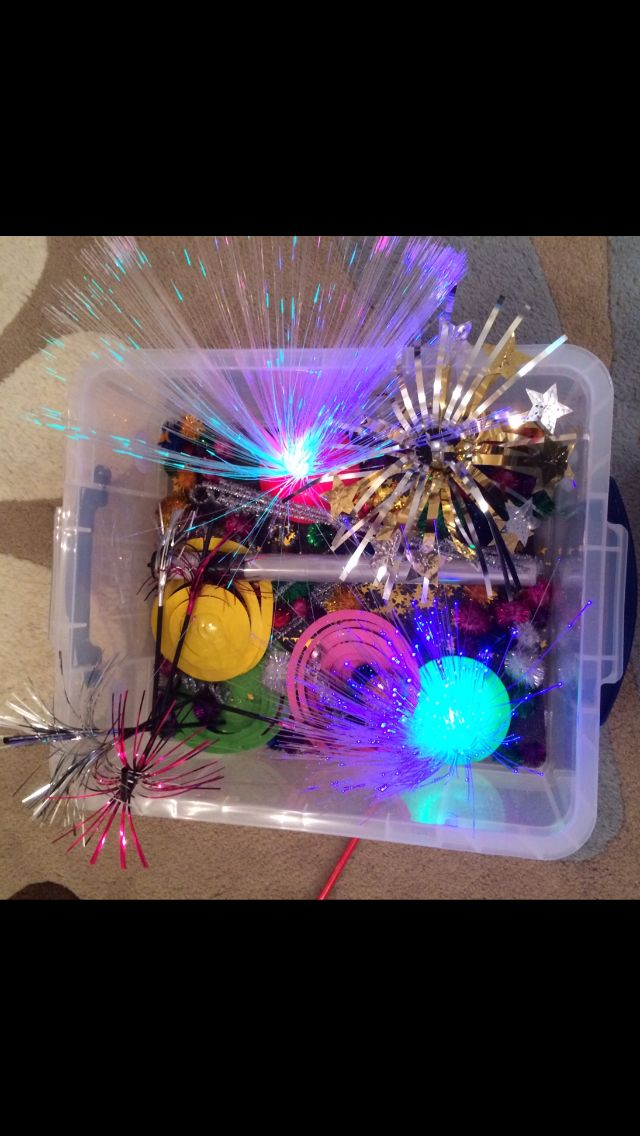 'Firework' sensory box. Contains: 2 optic fibre lights, 2 star foil table decorations, 3 'Catherine wheel' hanging party decorations, lots of sparkly pom-poms, gold stars, one lightsabre toy, straws with fringe decoration, silver pipe cleaners and black sparkly card to line the box