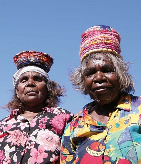 Martumili artists Jartarr Lily Long and Yuwali Janice Nixon at Kunkun near Well 33 of the Canning Stock Route. They design baskets to remind them of the piti [wooden dishes] they used to carry on their heads. They gather the minari [grass] from their Country along with coloured wool.