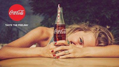 Woman holding a bottle of Coca-Cola for the Taste The Feeling campaign
