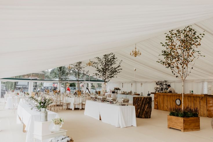 Bringing the outside in and what a difference it makes. Handmade bar and 'oak stump' tables made by the groom and his tree surgery business! Photo by Benjamin Stuart Photography #weddingphotography #trees #weddingdecor #receptiondecor #marqueewedding #diywedding #treesurgeon