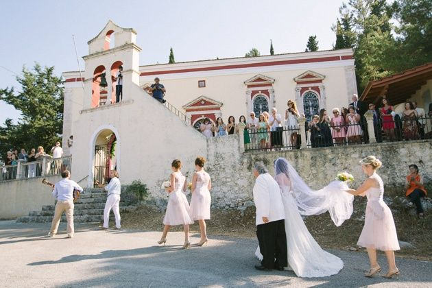 Bride being escorted by he bridesmaids and traditional Greek musicians to her wedding ceremony in a beautiful Greek Orthodox church in Kefalonia. Organised by Stella and Moscha weddings. Photo by Adrian Wood