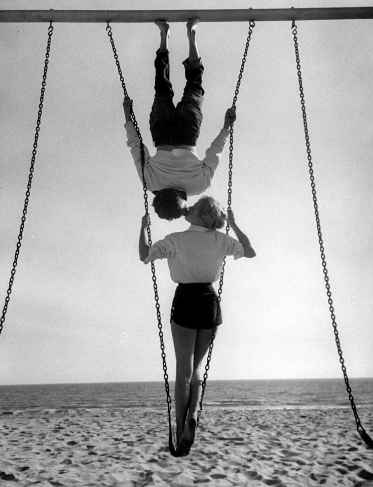 """Acrobat and actor, Russ Tamblyn (Top) on the beach with movie actress  Venetia Stevenson (entitled """"Swingers"""")."""