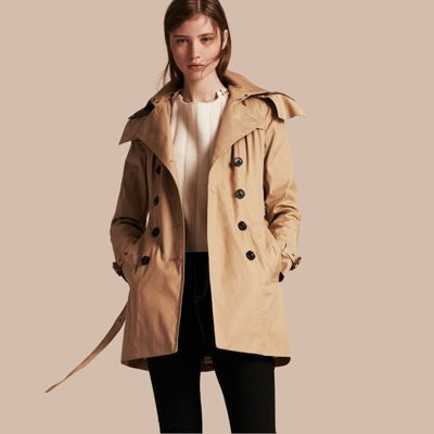 A protective trench coat crafted from fine canvas cotton. Lining the slim silhouette, a button-out quilted warmer and detachable hood provide additional protection from the elements. Epaulettes, a gun flap and belted cuffs reference the original Burberry trench coat, and the design is complete with a distinctive check undercollar.