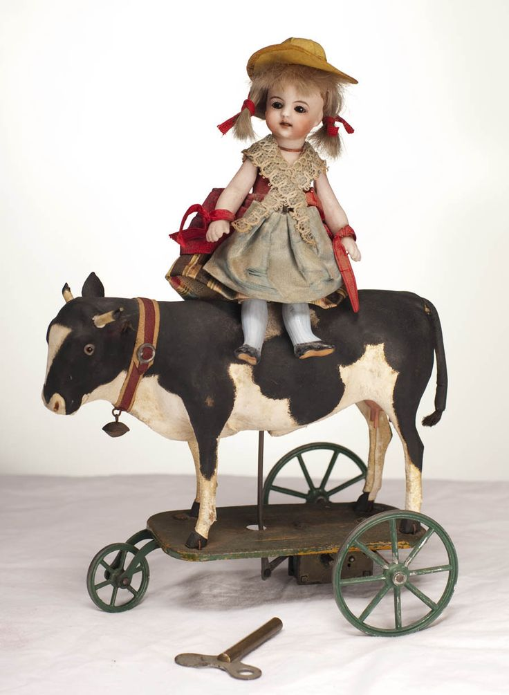 doll sitting on cow