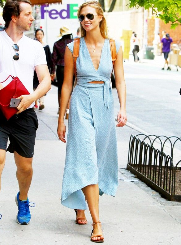 Karlie Kloss wears a blue wrap dress by The Reformation, Ray-Ban aviators, and tan leather accessories