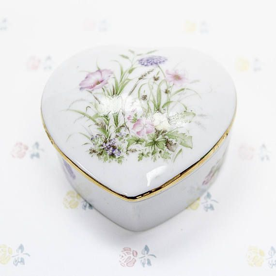 A white porcelain jewelry/trinket box in the shape of a heart, with multi-colored floral motifs and gold trim along the lid edge. Made in Japan seal remains on the bottom (though slightly ripped)  Dimensions: 10x8.5x2cm  Condition: Item is in good used condition, showing only very